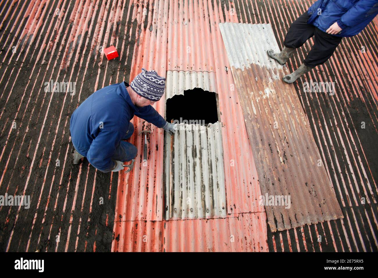 Farmers Bjarni Thorvaldsson and Thorgrimur Bjarnason (R) inspect a hole in a barn roof as they work to clean off volcanic ash that has accumulated from an erupting volcano near Eyjafjallajokull April 18, 2010.  REUTERS/Lucas Jackson (ICELAND - Tags: DISASTER ENVIRONMENT) Stock Photo