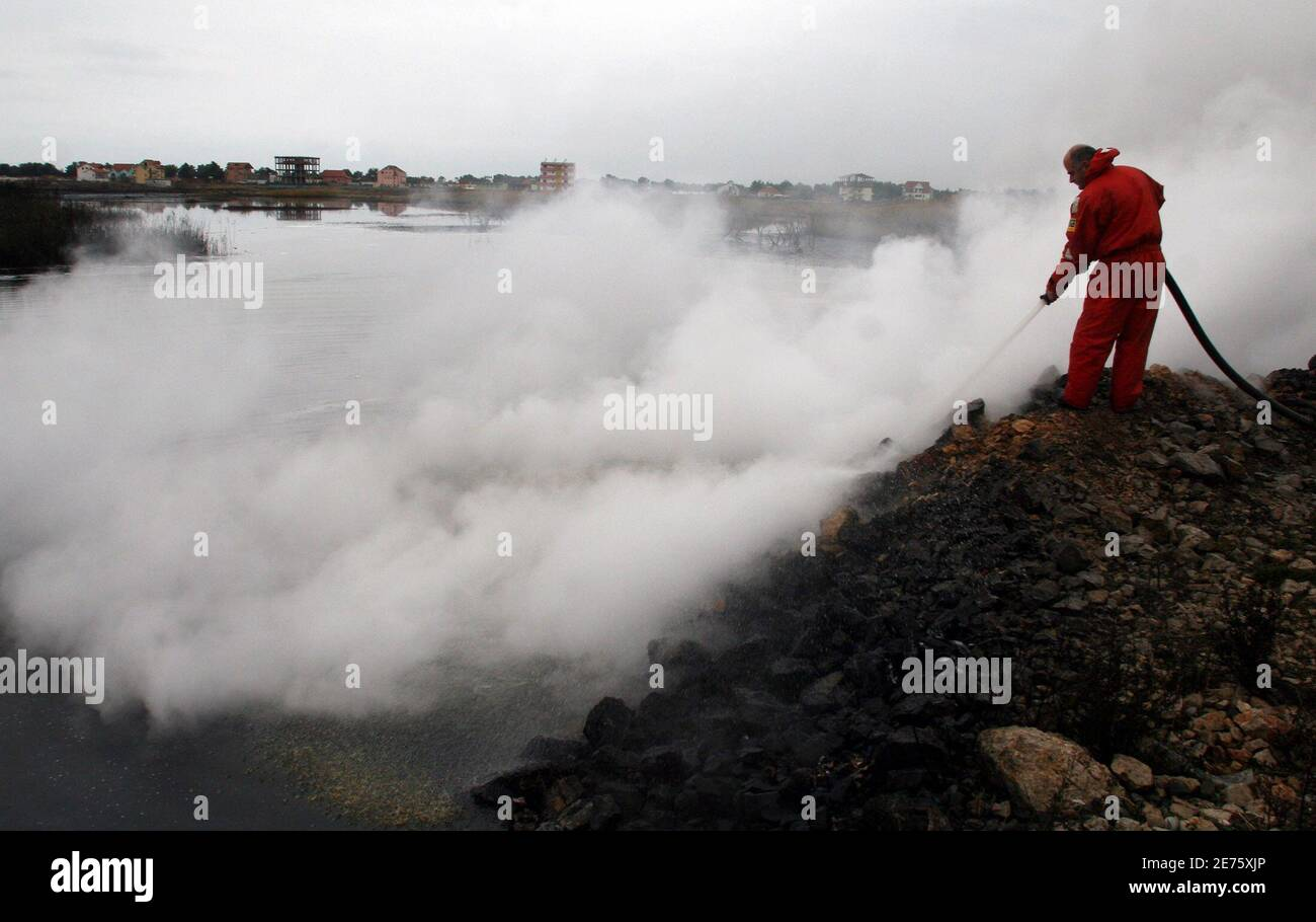An Albanian firefighter tries to contain a fire that burnt a fuel deposit in the port city of Shengjin, some 70 km (44 miles) northwest of capital Tirana December 18, 2006. Firefighters worked all Sunday using retardant foam water and sand to prevent the fire from spreading to two bigger deposits. REUTERS/Arben Celi (ALBANIA) Stock Photo