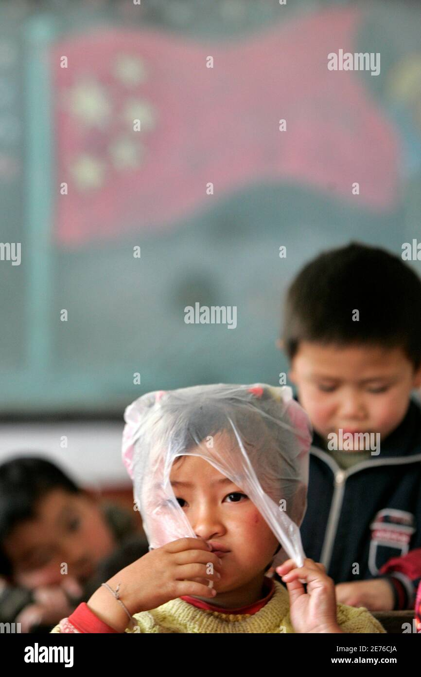 A girl relaxes during playtime at a rural primary school in Nanhui district on the outskirts of Shanghai March 2, 2007. After years of focus on urban schools and higher education, basic schooling in rural areas has finally become a priority for a government trying to address a rural-urban wealth gap in China that is contributing to social unrest.  REUTERS/Aly Song (CHINA) Stock Photo