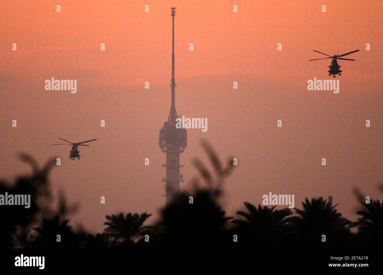 U.S. military helicopters patrol over Baghdad during sunset December 14, 2006. REUTERS/Nikola Solic     (IRAQ) Stock Photo