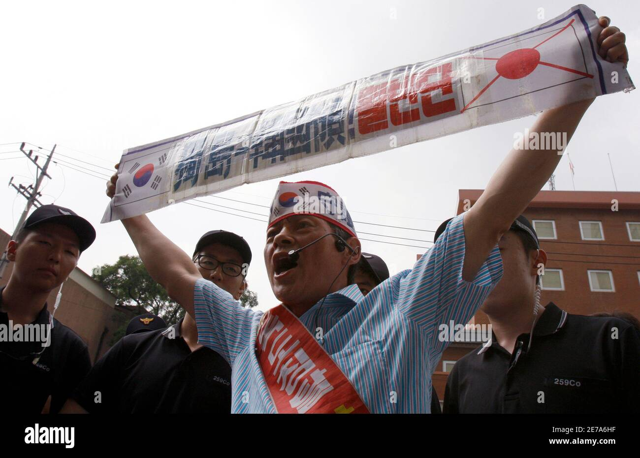 """A protester surrounded by police holds a banner as he shouts slogans during an anti-Japan protest against Japan's sovereignty claim over a group of desolate volcanic islets Seoul and Pyongyang call Dokdo and Tokyo calls Takeshima, in front of Japanese embassy in Seoul July 14, 2008. Japan formally informed South Korea of its plan to describe Dokdo, the islets which lie almost midway between the mainlands of Korean peninsula and Japan, as Japan's territory, Seoul's government officials said on Monday, according to local media. The banner reads: """"Dokdo is South Korean territory"""".   REUTERS/Lee J Stock Photo"""