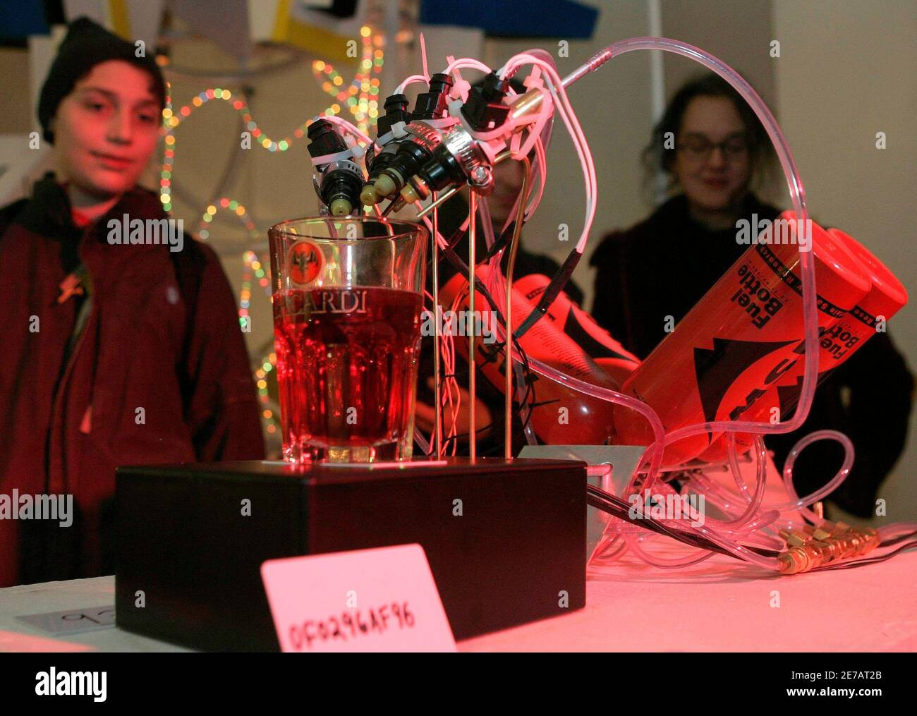 """Visitors look at  """"The External Combustion Engine""""  December 7, 2006, made by Jacob Appelbaum, David Fine and Jonathan Moore of the U.S., one of around 30 robots at Vienna's annual Roboexotica, which showcases how home-built machines deal with the modern pastime of hanging out in bars.  Picture taken December 7, 2006. TO ACCOMPANY STORY AUSTRIA-ROBOTS/   REUTERS/Herwig Prammer (AUSTRIA) Stock Photo"""