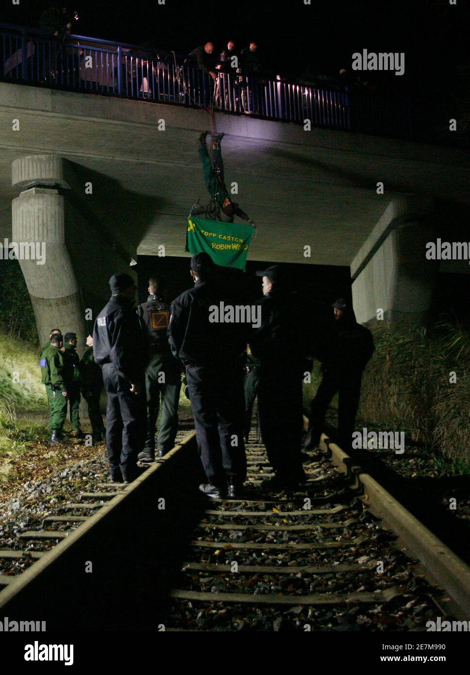 """German police officers remove an anti-nuclear activist from the German environmental organisation Robin Wood hanging from a rope over a railway track in Oldendorf, between Lueneburg and Dannenberg November 10, 2008. The controversial shipment of eleven Castor containers with spent German nuclear fuel arrived in Dannenberg on Monday and will be loaded onto trucks before transportation to the nearby Gorleben intermediate storage facility in northern Germany after it left the French reprocessing plant of La Hague on Friday. The banner reads """"Stop Castor"""". REUTERS/Christian Charisius (GERMANY) Stock Photo"""