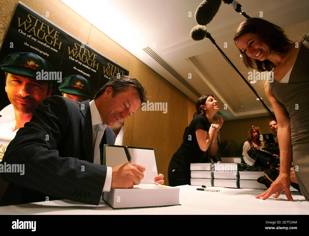 """Former Australian cricket team captain Steve Waugh signs a copy of his autobiography for a cricket fan in Sydney October 23, 2005. Waugh, Australia's Test cricket captain from 1999 to 2004, has penned a book entitled """"Out of My Comfort Zone"""" in which he reveals insights into life on and off the field during the time he headed a dominant team. REUTERS/Will Burgess Stock Photo"""