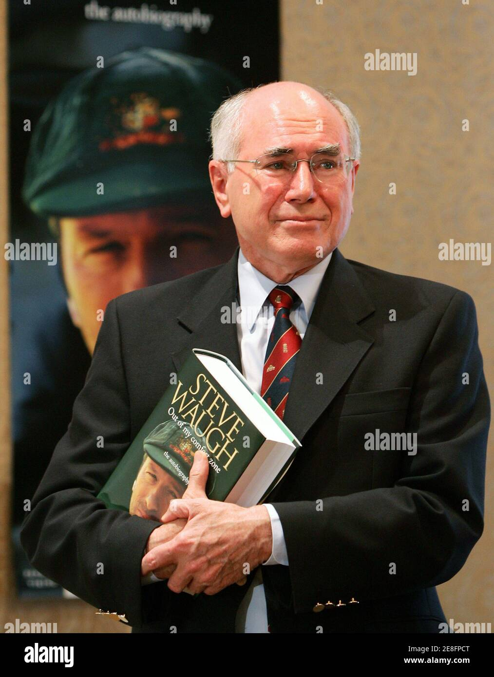 Australia's Prime Minister John Howard holds his copy of former Australian cricket team captain Steve Waugh's autobiography after launching the book in Sydney October 23, 2005. Waugh, Australia's Test cricket captain from 1999 to 2004, has penned the book entitled 'Out of My Comfort Zone' in which he reveals insights into life on and off the field during the time he headed a dominant team. REUTERS/Will Burgess Stock Photo