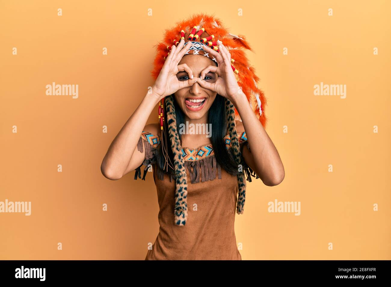 Young brunette woman wearing indian costume doing ok gesture like binoculars sticking tongue out, eyes looking through fingers. crazy expression. Stock Photo