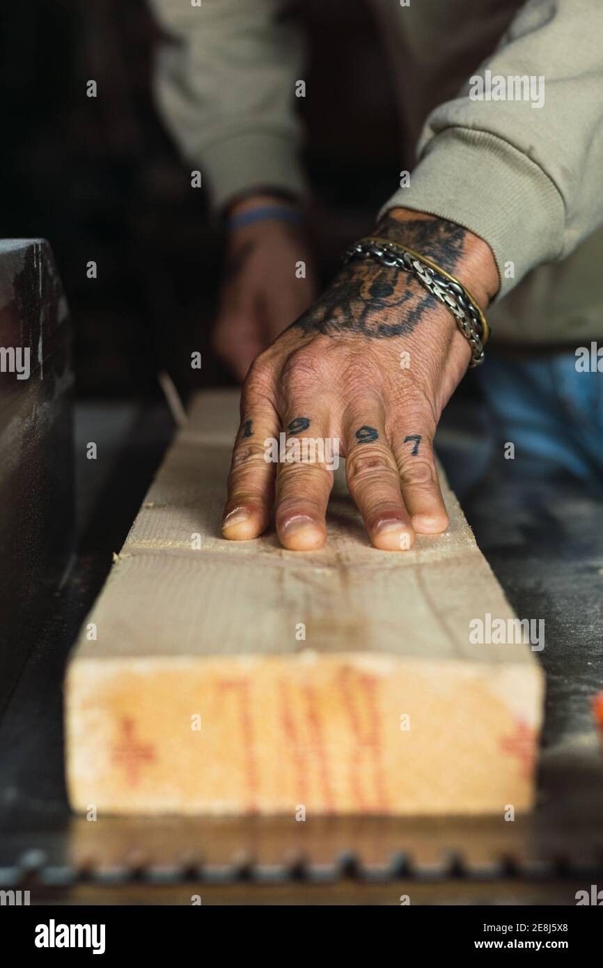 Unrecognizable crop male woodworker without a thumb processing piece of wood at workbench while working in joinery Stock Photo