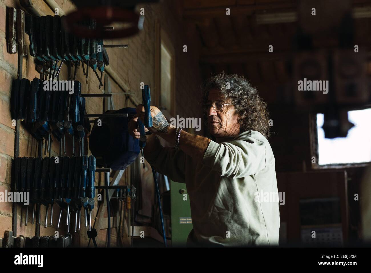 Side view of mature male joiner taking carpentry clamp from shelf in shabby woodworking workshop Stock Photo