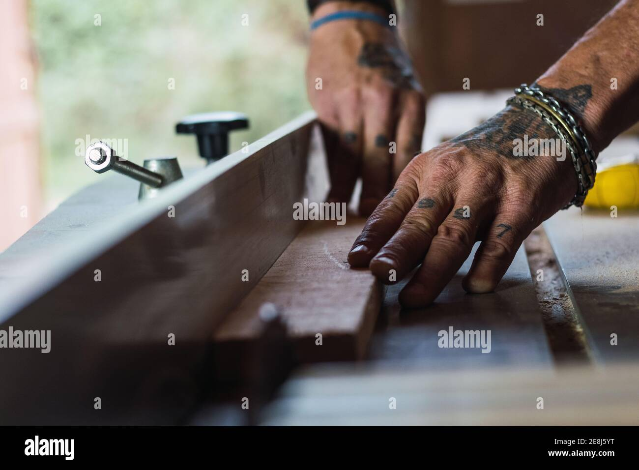 Closeup of crop unrecognizable male without a thumb joiner cutting wood with circular saw in joinery Stock Photo