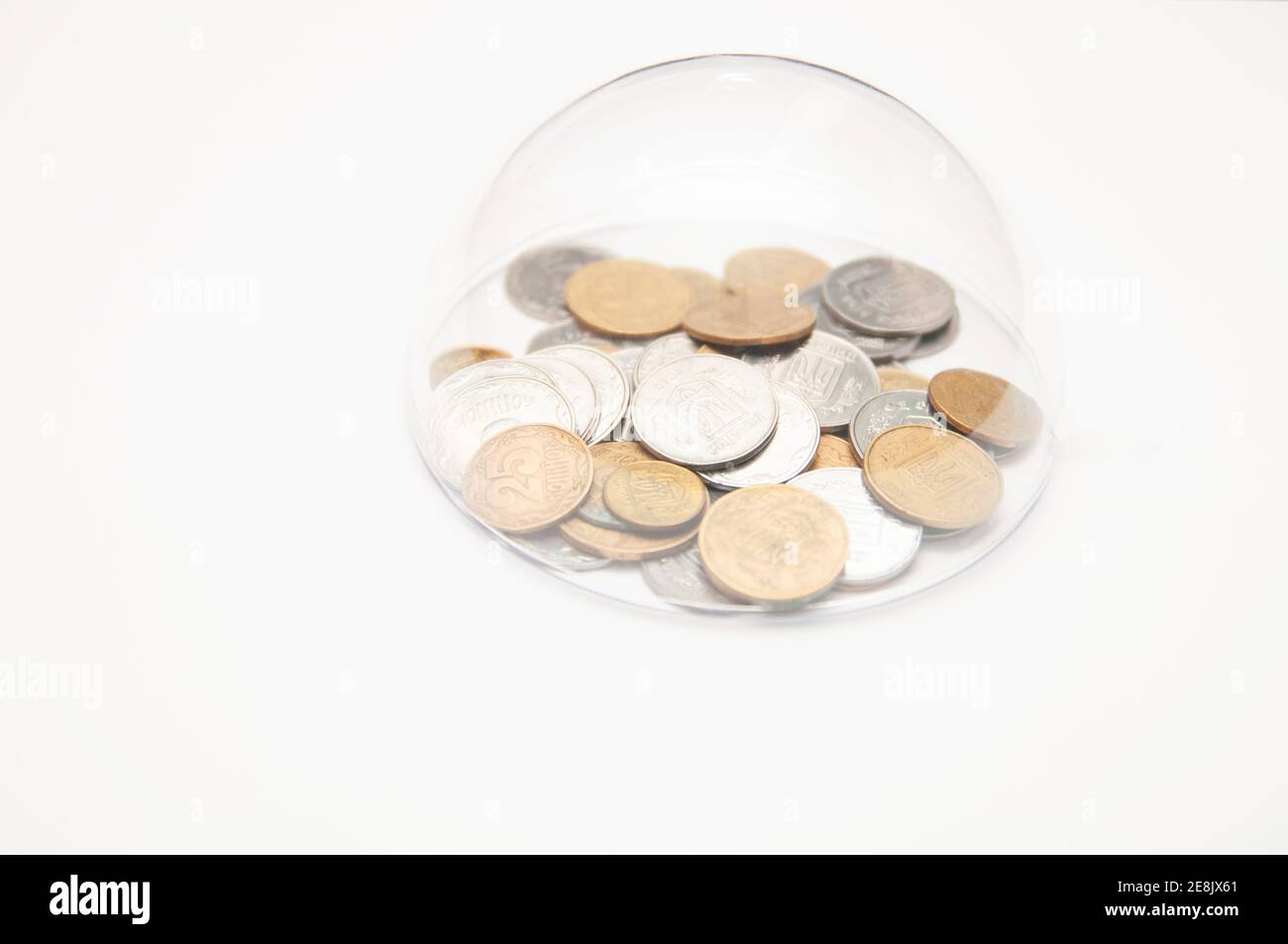 metal coins are grouped under a glass semicircle on a white background Stock Photo