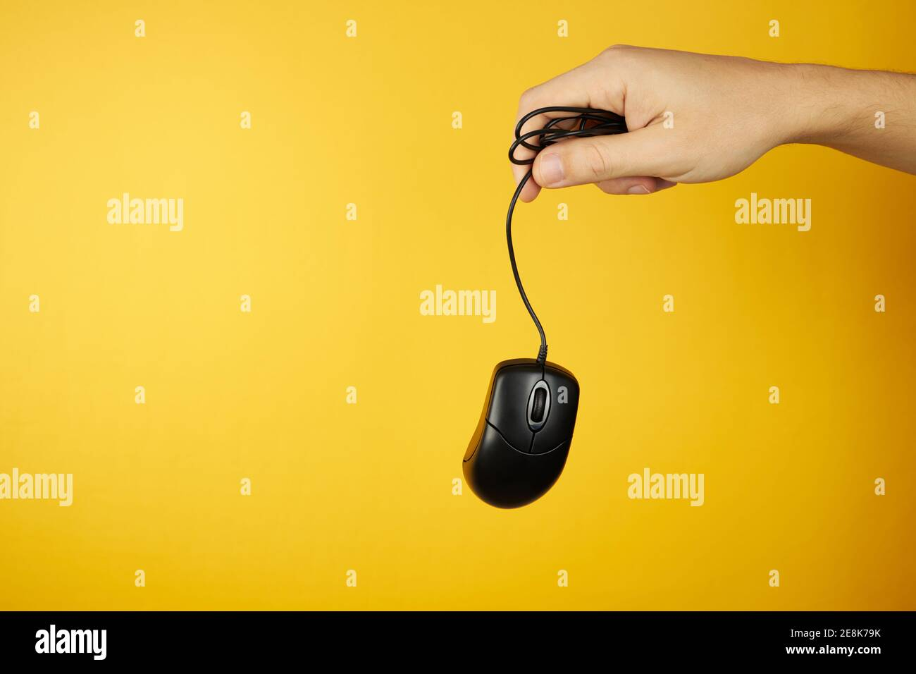 The black computer mouse at hand on a yellow background with copy space. hardware maintenance service concept Stock Photo