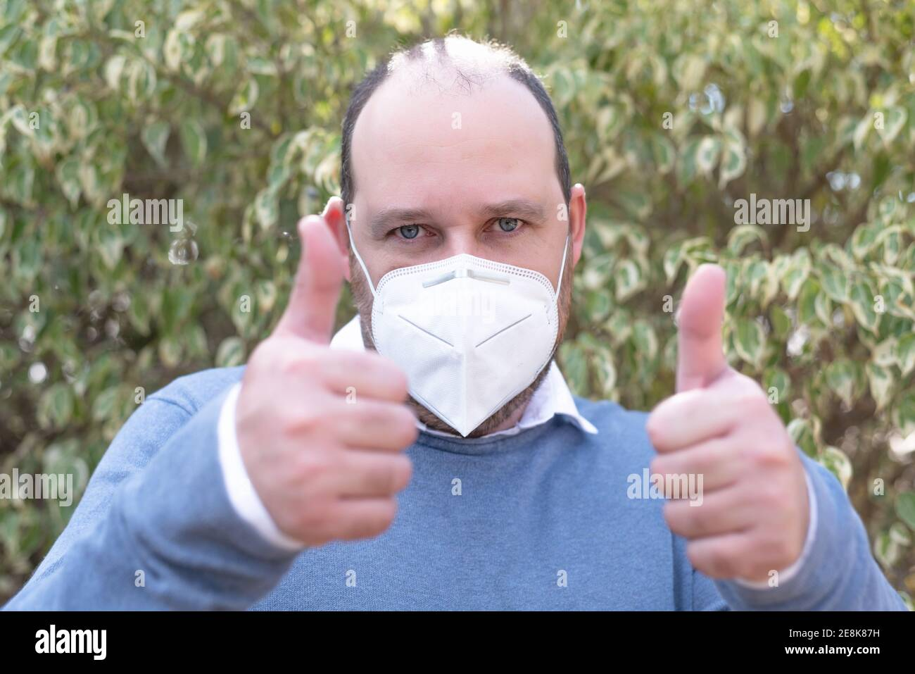 I like! Portrait of optimistic handsome man with medical mask in blue t-shirt showing thumbs up gesture and smiling, that is, well done, good job Stock Photo