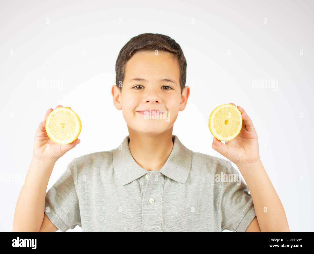 Portrait of lovely caucasian young boy shows two lemon slices.Boy look to a camera. Stock Photo