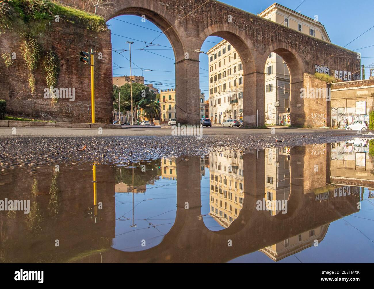 Frequent rain showers create pools in which the wonderful Old Town of Rome reflect like in a mirror. Here in particular Piazza di Porta Maggiore Stock Photo