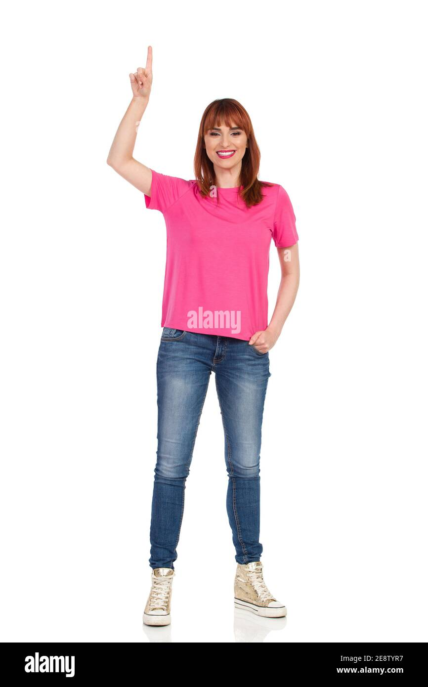Young woman in pink shirt, jeans and gold sneakers is standing, pointing up and smiling. Front view. Full length studio shot isolated on white. Stock Photo