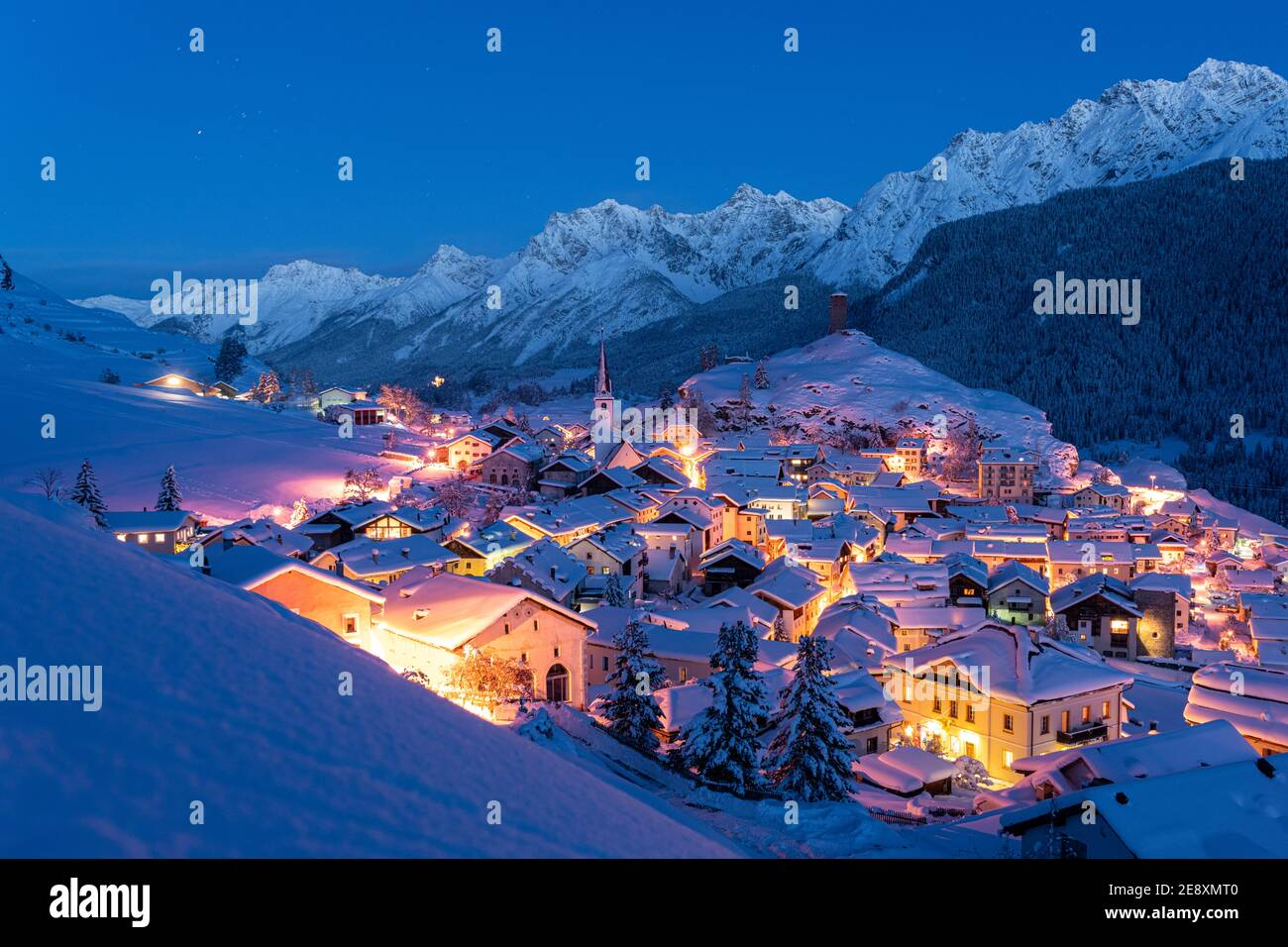 Traditional alpine village of Ardez covered with snow at dusk, canton of Graubunden, Engadine, Switzerland Stock Photo
