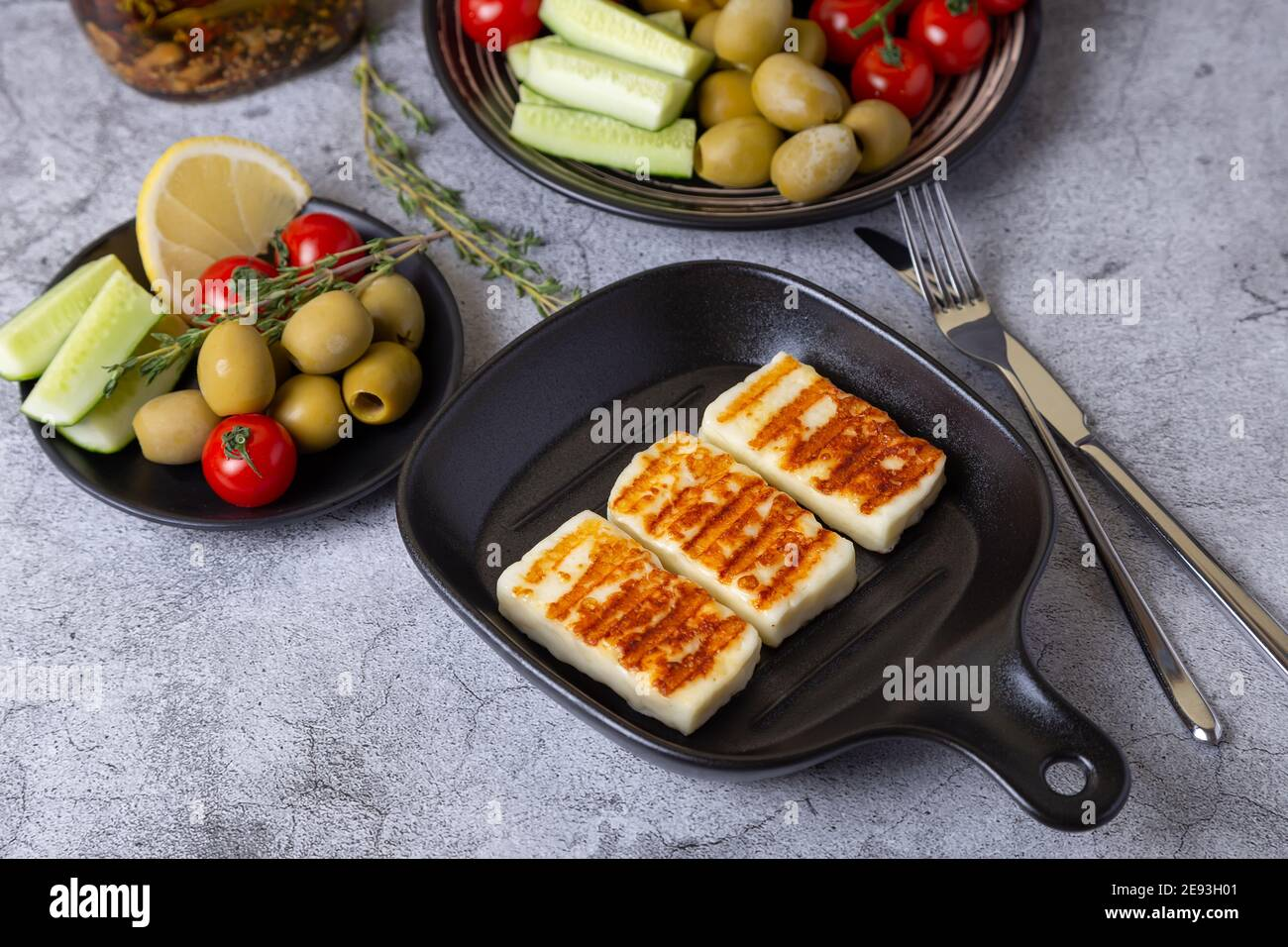 Grilled haloumi cheese on a black pan with olives, tomatoes, cucumbers and pepperoni. Close-up. Stock Photo