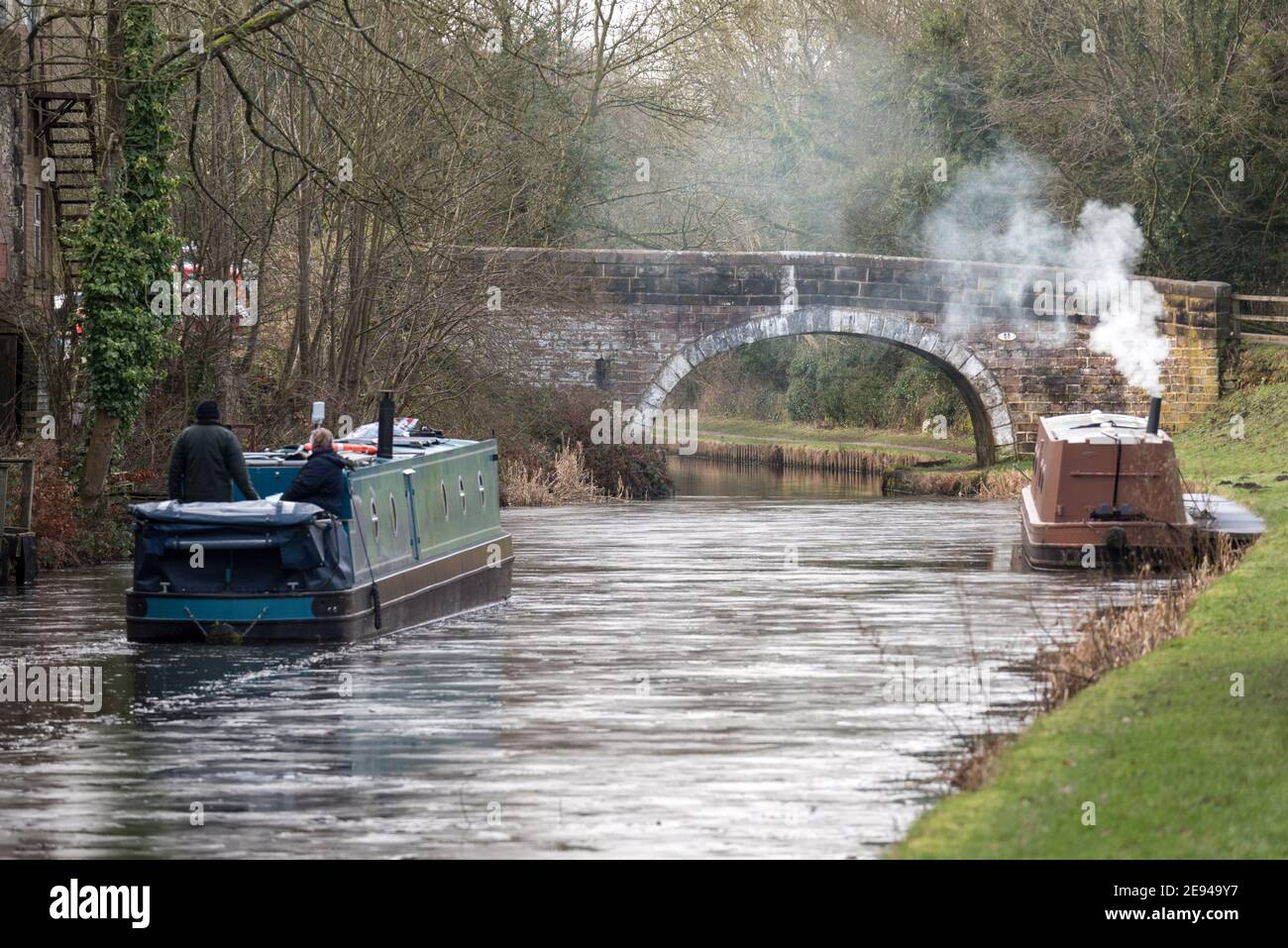 A narrowboat cutting a path through the ice on a frozen canal. Stock Photo