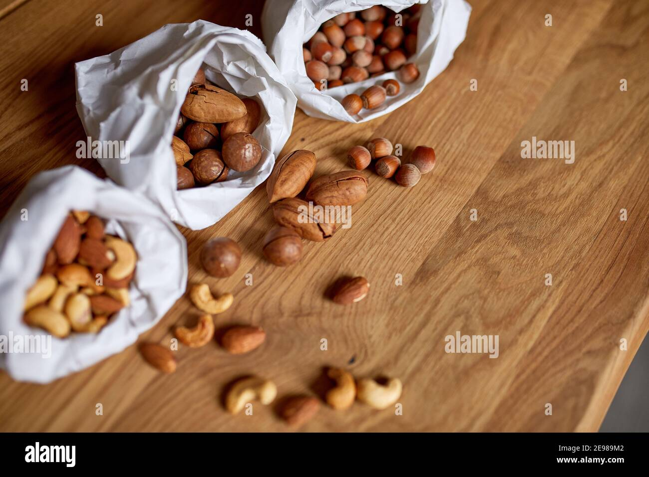 Top view Various sort of nuts on the table in a paper bag on wooden background, shopping grocery concept, nuts delivary, Zero Waste Food Shopping. Cop Stock Photo