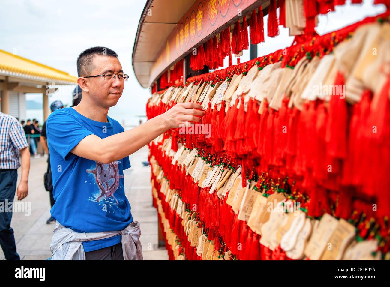 Chinese man is looking at wooden planks for writing prayers. Chinese red and wooden plates for wishes. Buddhist center Nanshan. Asian traditions. Stock Photo