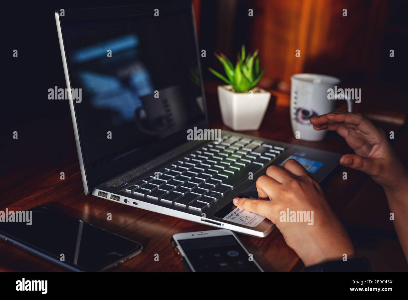 IT professional woman working from home with Laptop and Phones with a hot cup of coffee beside and a green plant Stock Photo