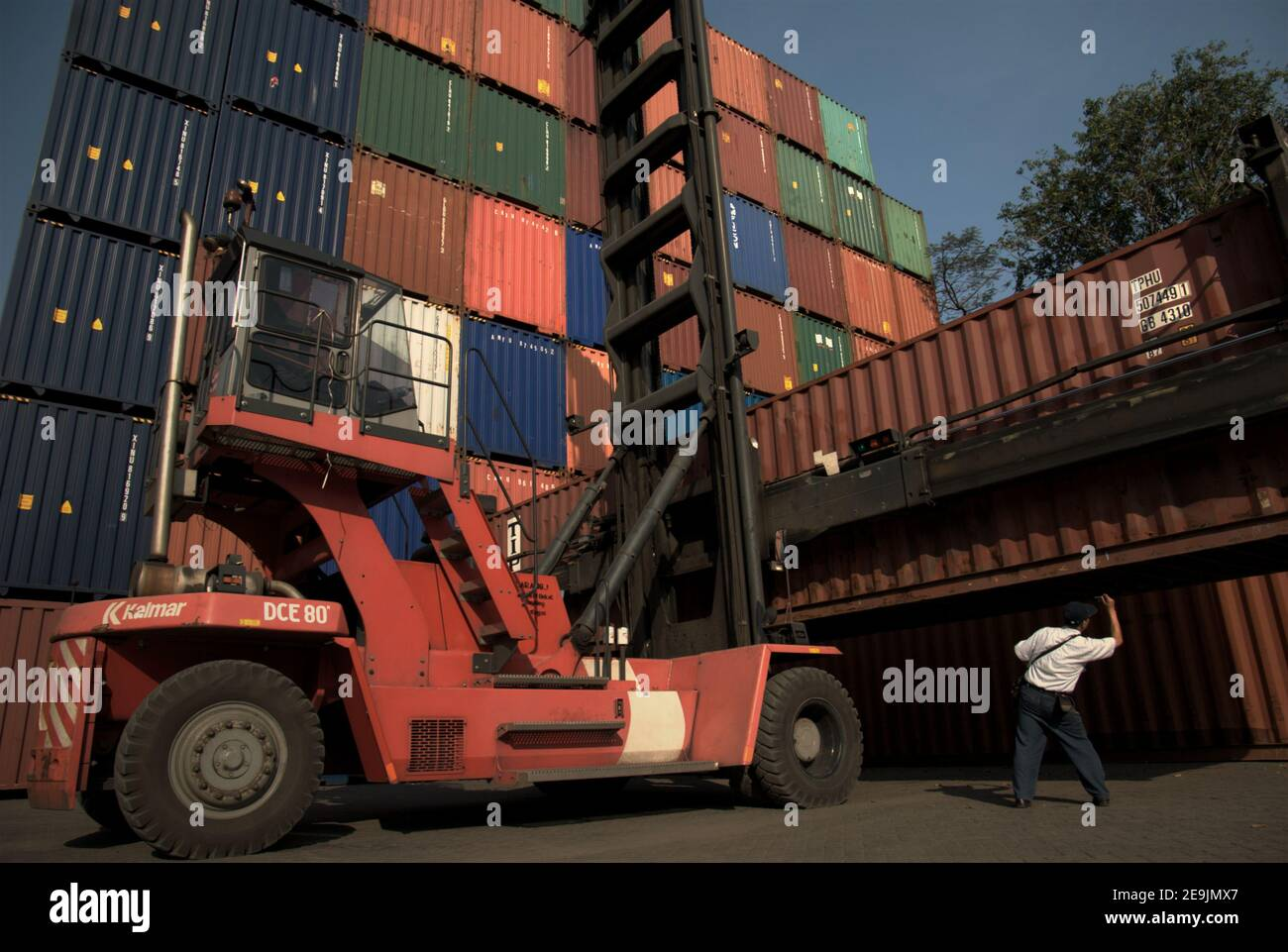 Workers arranging shipping containers at the Port of Jakarta's shipping container terminal. Jakarta, Indonesia. Stock Photo