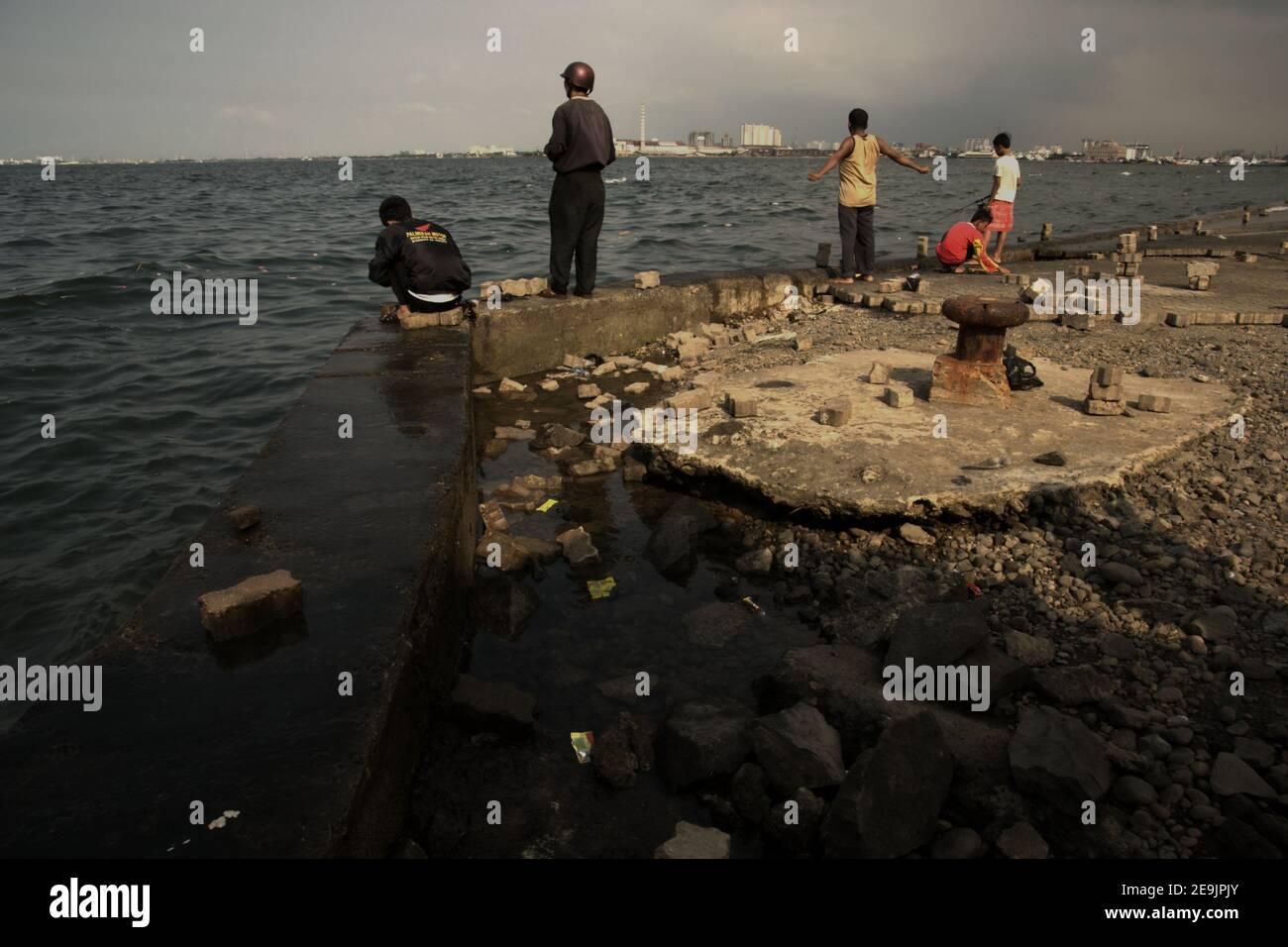 People having outdoor recreation by fishing from an abandoned harbour platform in Muara Baru area, Penjaringan, Jakarta, Indonesia. Stock Photo