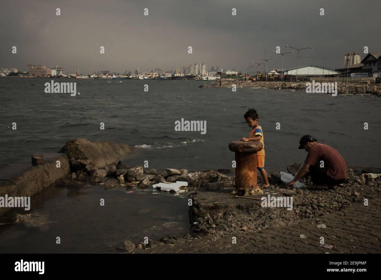 Weather and sea tides have left a harbour platform damage then abandoned, in the coastal area of Jakarta, where a man and child getting ready to have an outdoor recreation by fishing. Muara Baru area, Penjaringan, Jakarta, Indonesia. Stock Photo