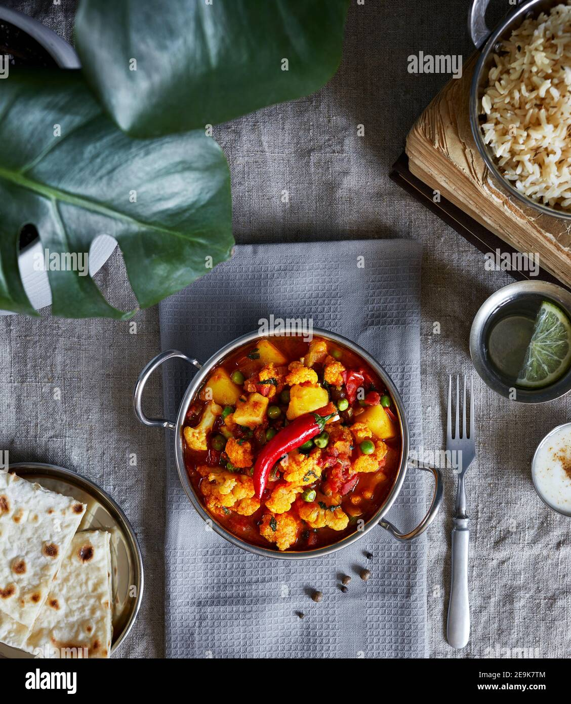 Aloo gobi traditional Indian food from cauliflower and potato decorated with red chili served with brown rice, dahi, lemon water and chapati on the ta Stock Photo