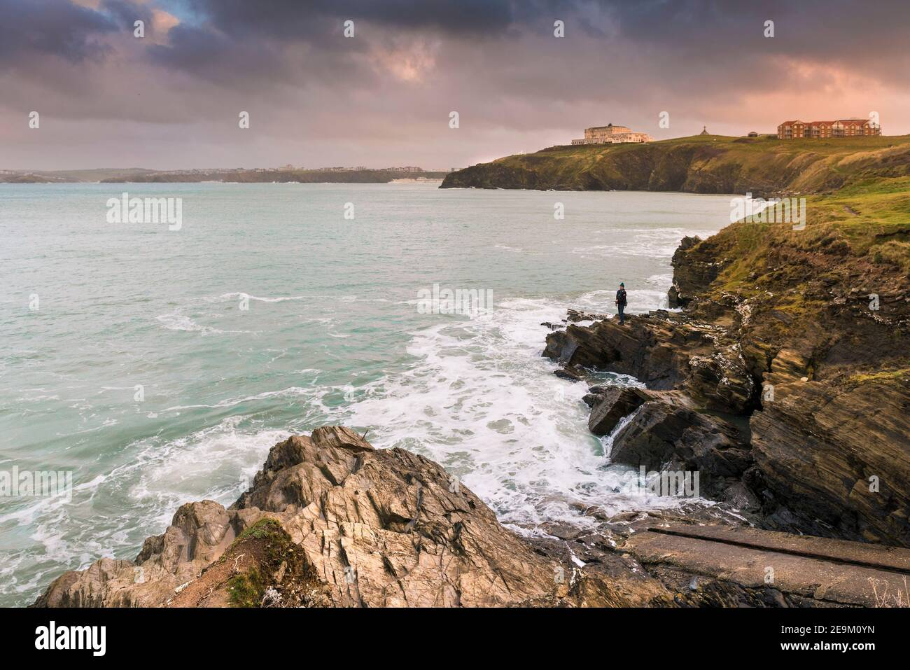 Warm evening light over an angler fishing off rocks on the coastline of Newquay Bay in Cornwall. Stock Photo