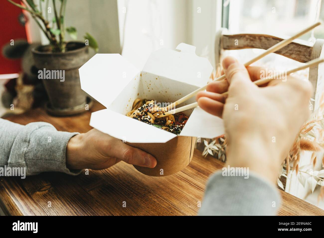 Close-up of noodles in a box. Takeaway food. Person eats food with chopsticks. Stock Photo