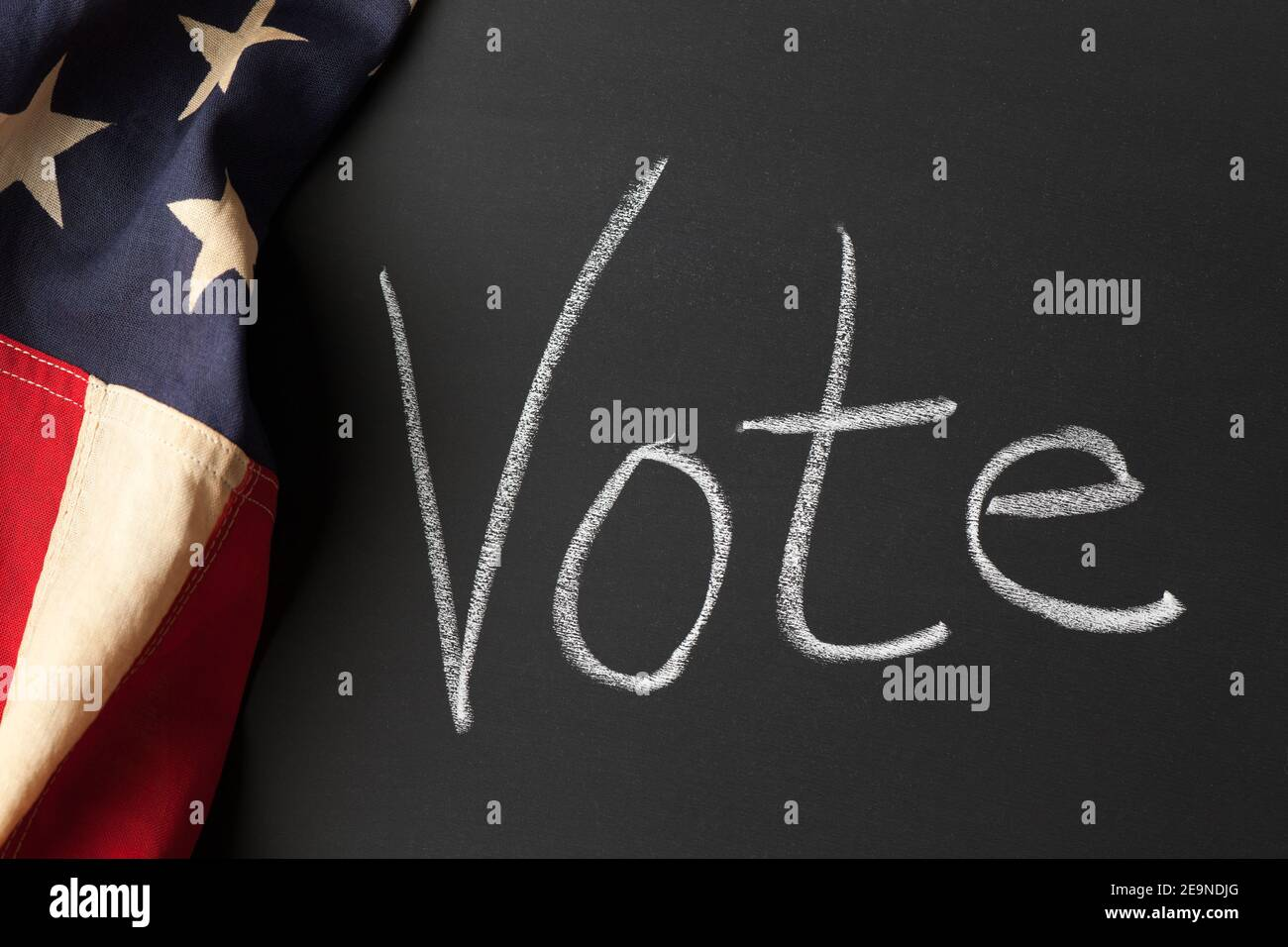 A vote sign written on a chalkboard with vintage American flag Stock Photo