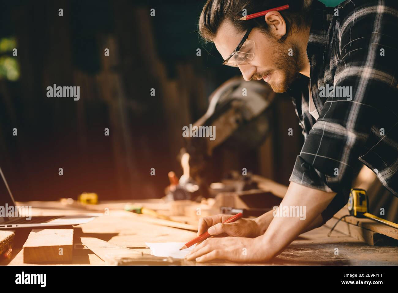 Happy Carpenter smiling to sketch design wooden furniture in wood workshop professional look high skill real authentic handcrafted working people. Stock Photo