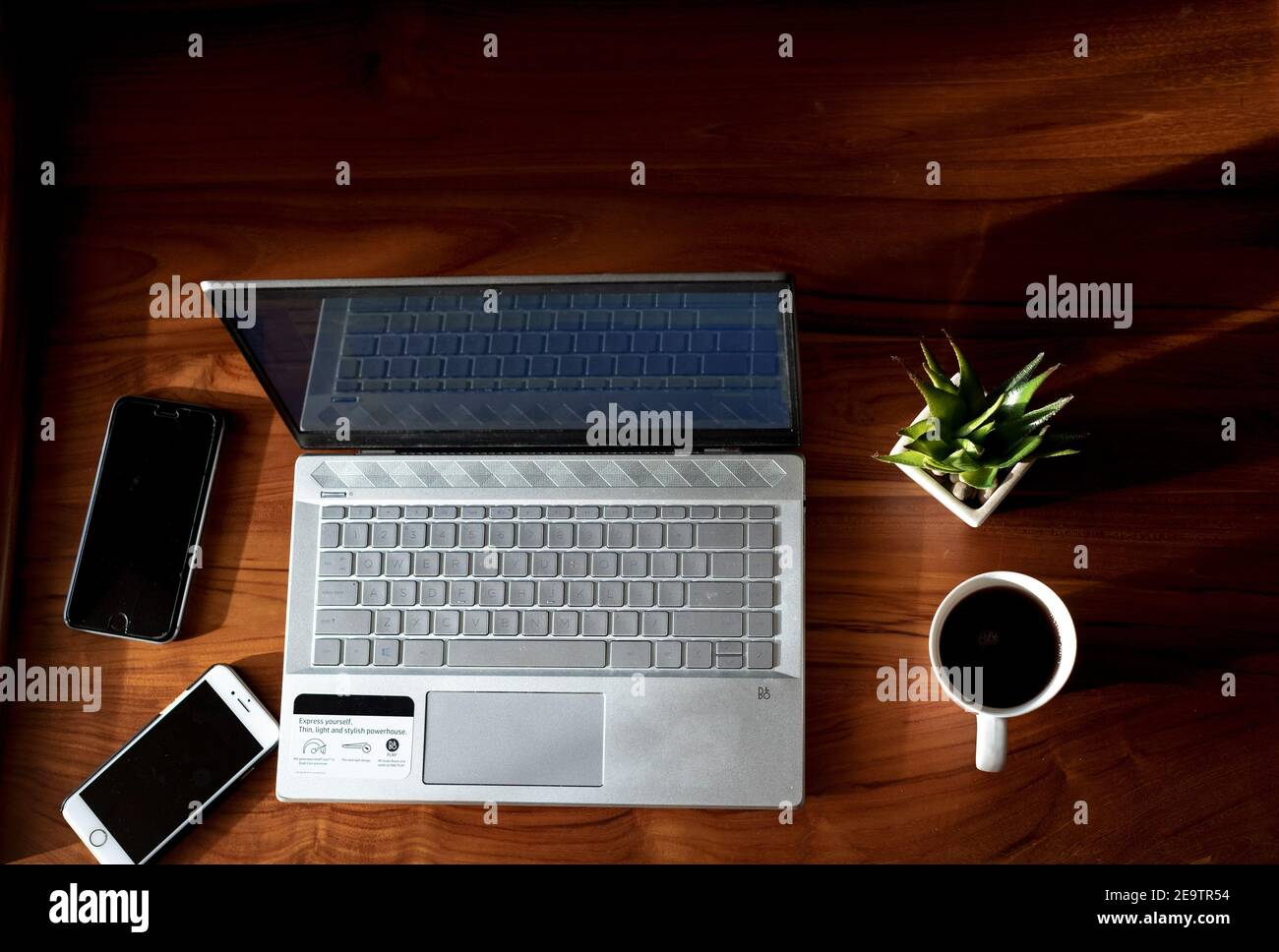 Working from home with Laptop and Phones with a hot cup of coffee beside and a green plant Stock Photo