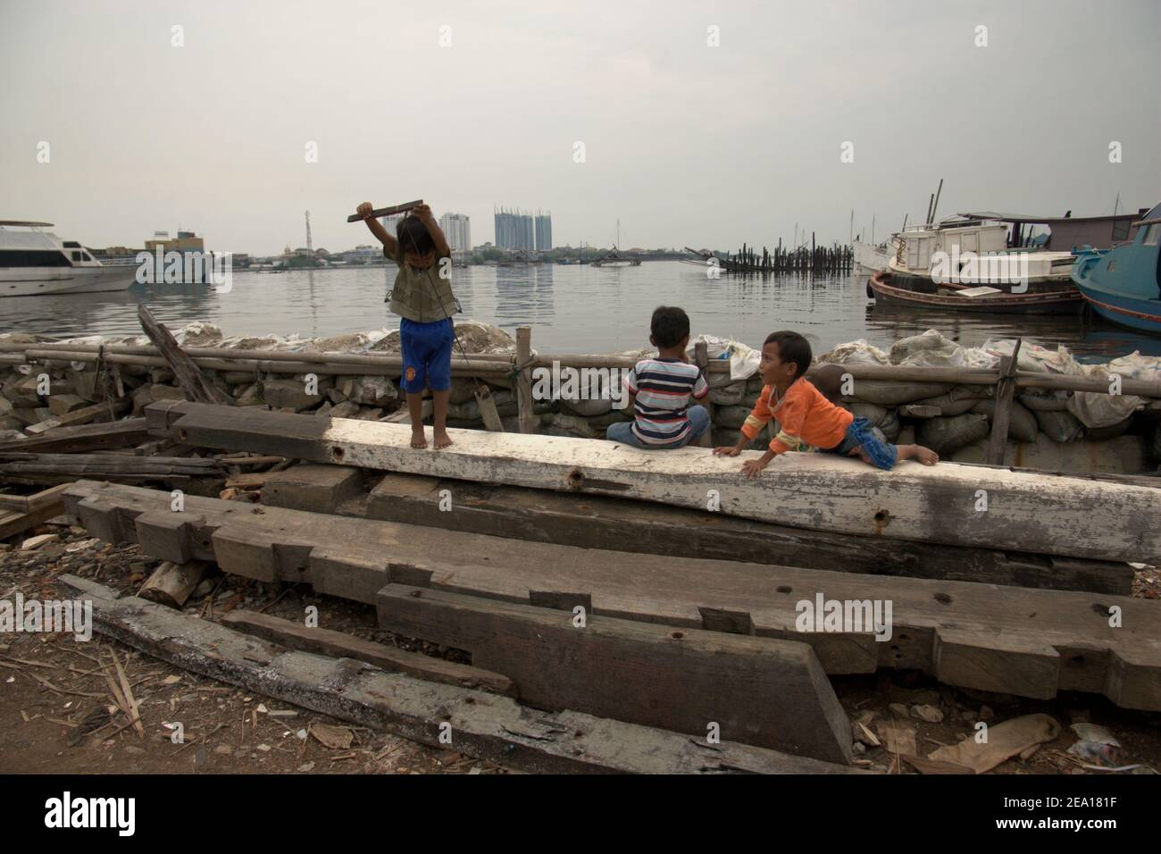 A group of children having a recreation behind the coastal protection structure protecting their neighbourhood from sea water floods in Muara Baru area, in the coastal area of Jakarta, Indonesia. Archival photo. Stock Photo