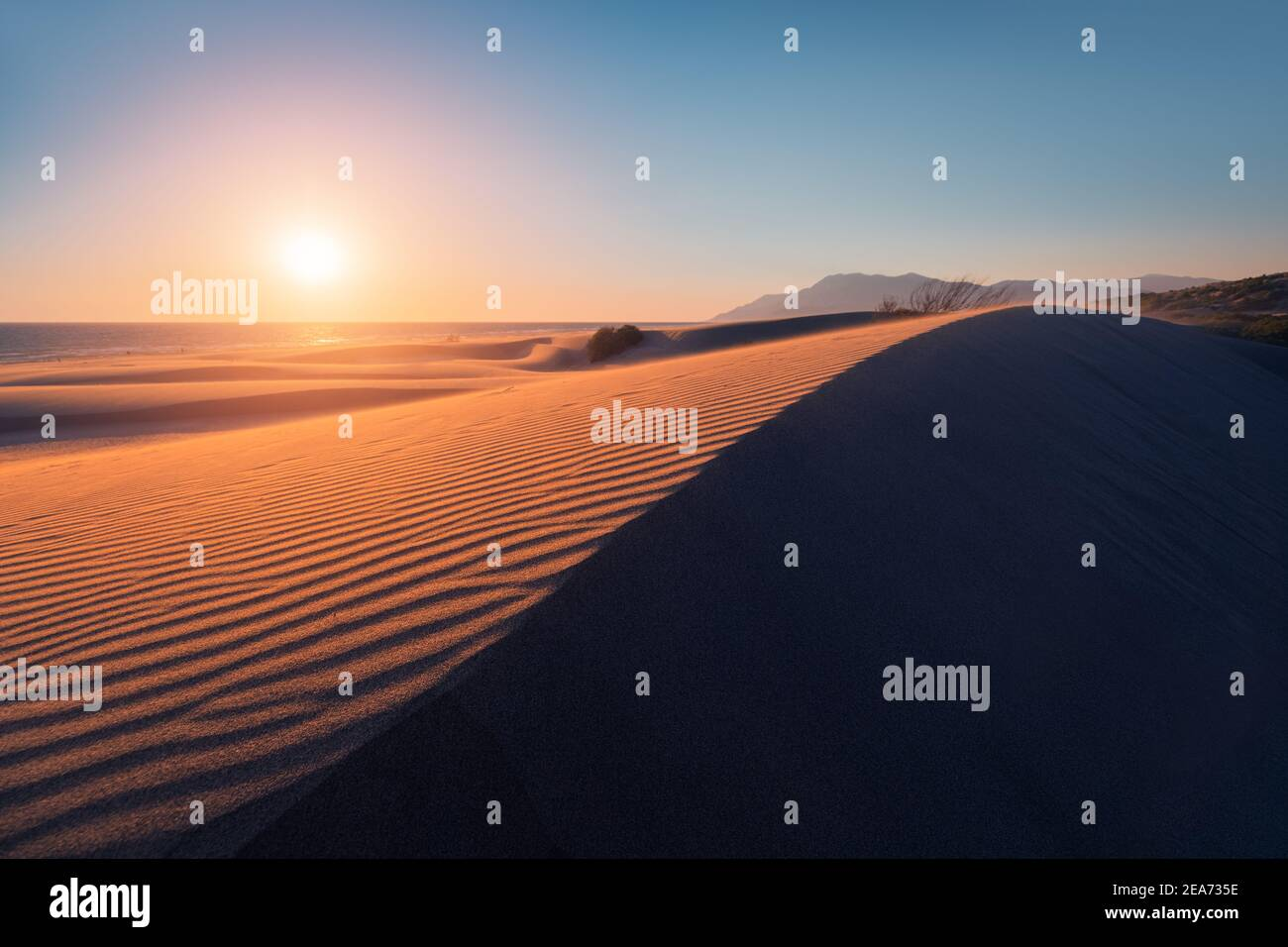 Atmospheric and mystical moody light of the sunset sunbeam illuminated the slope of a sand dune somewhere in the depths of the Sahara Desert Stock Photo