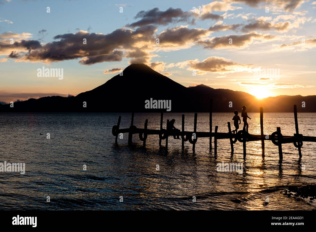 Silhouette of children running on dock of Lake Atitlan with San Pedro Volcano in the distance Stock Photo