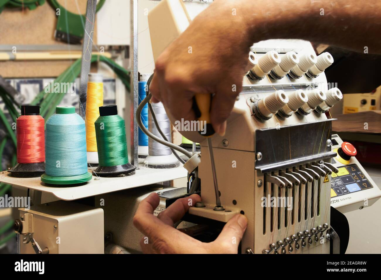 Mechanical and electrical specialist technician of embroidery machines Stock Photo