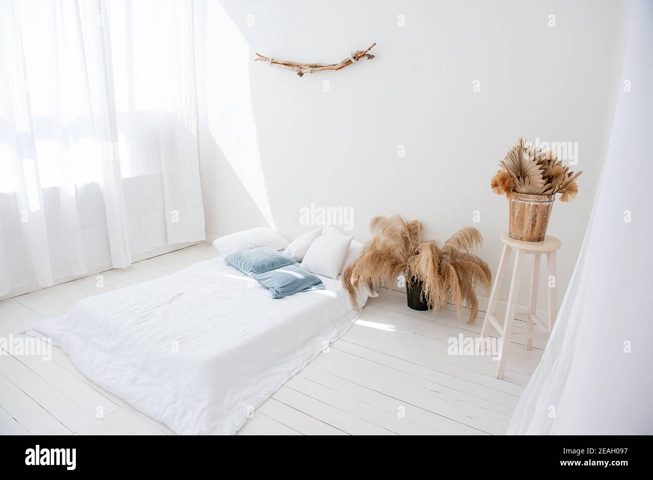 Minimalistic white loft in Scandinavian interior style. There is bed on wooden floor, light airy tulles on the windows, there is pampas grass in vases Stock Photo