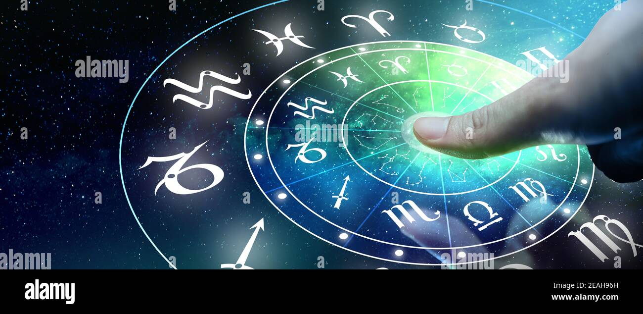 Astrological zodiac signs inside of horoscope circle. Man or Woman touching screen Zodiac signs hologram. Astrology concept. Stock Photo