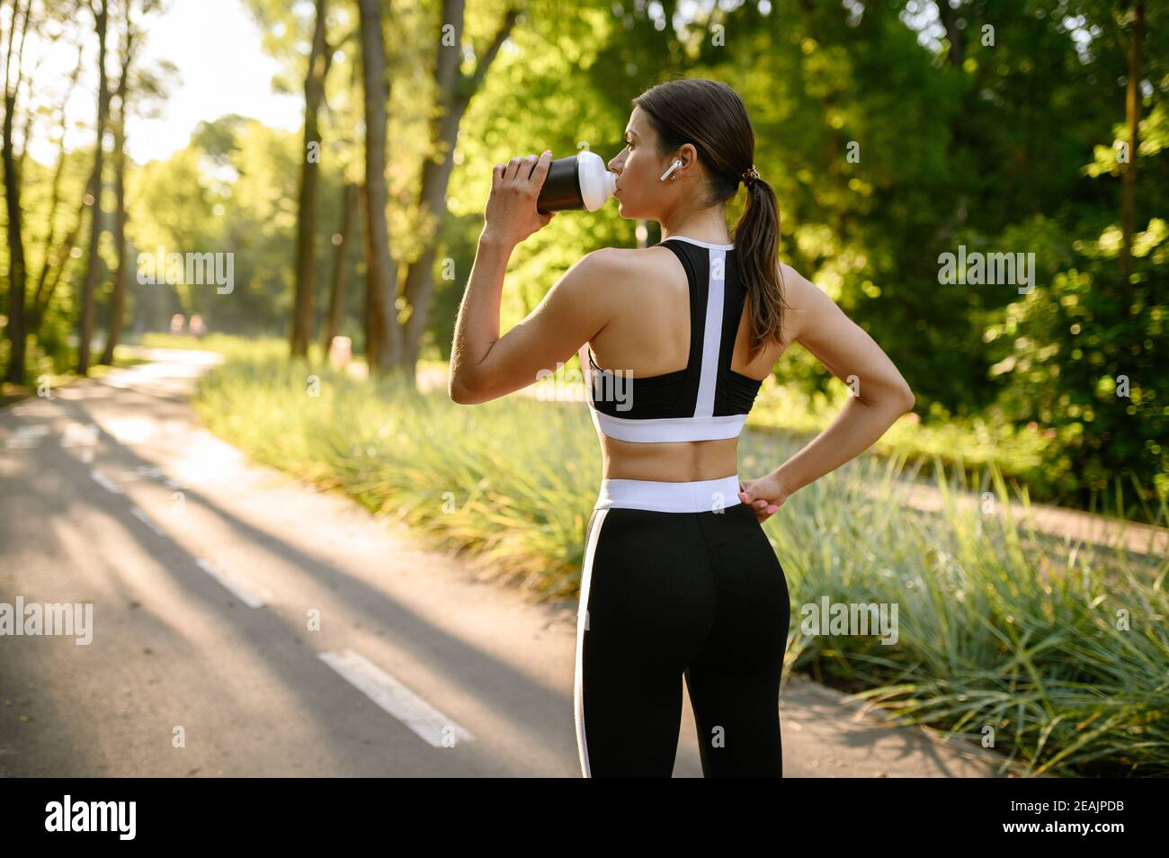 Morning training in park, woman drinks water Stock Photo
