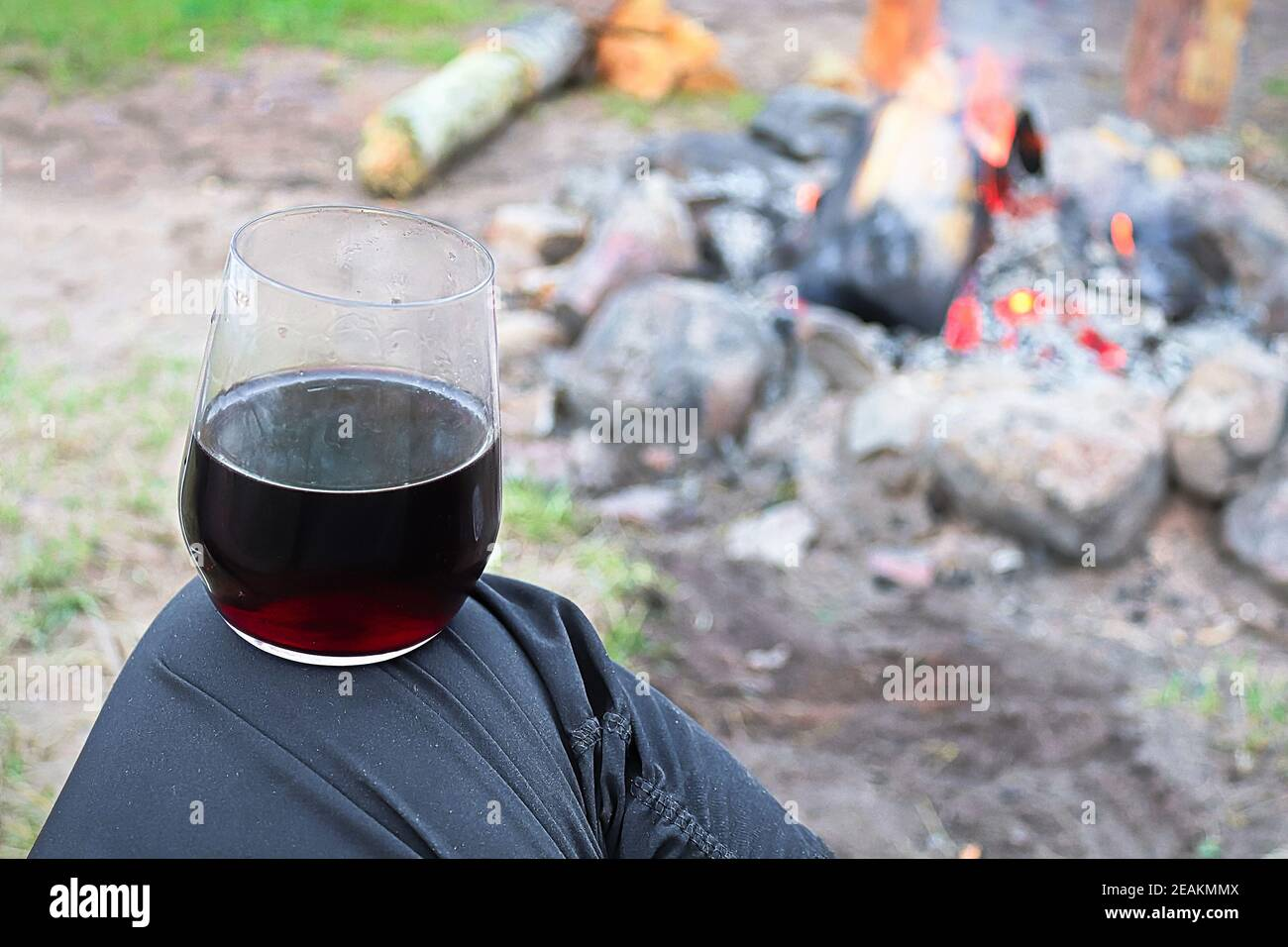 Balancing a glass of wine on a knee against a campfire Stock Photo