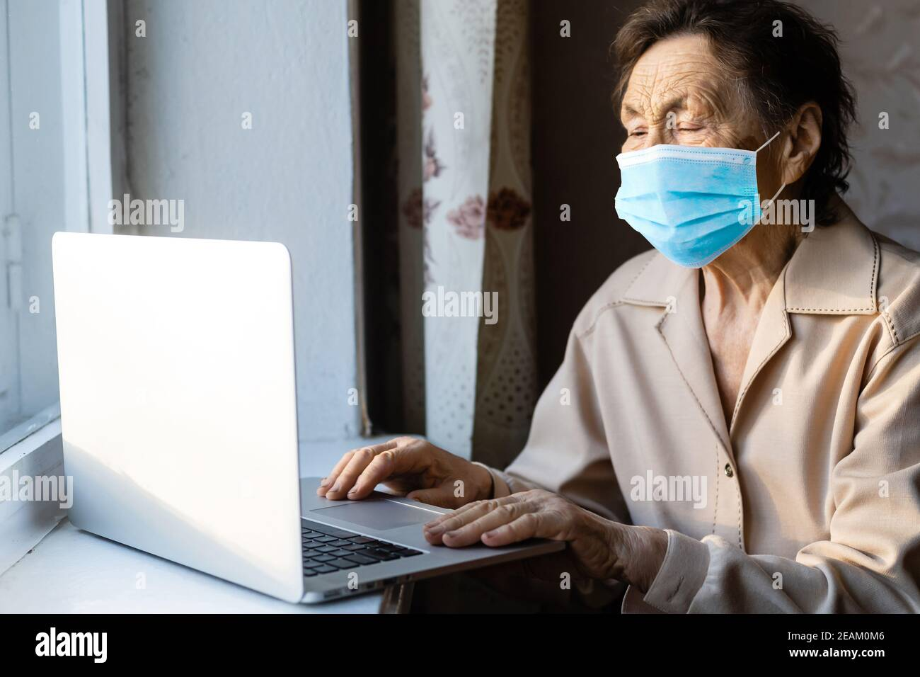 an elderly woman in a mask near the window with a laptop Stock Photo