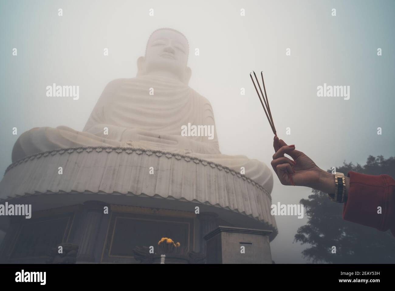 Buddha image with incense. Three incense sticks in a woman's hand against a big Buddha in the fog. Bana hill. Vietnam. Danang. Stock Photo