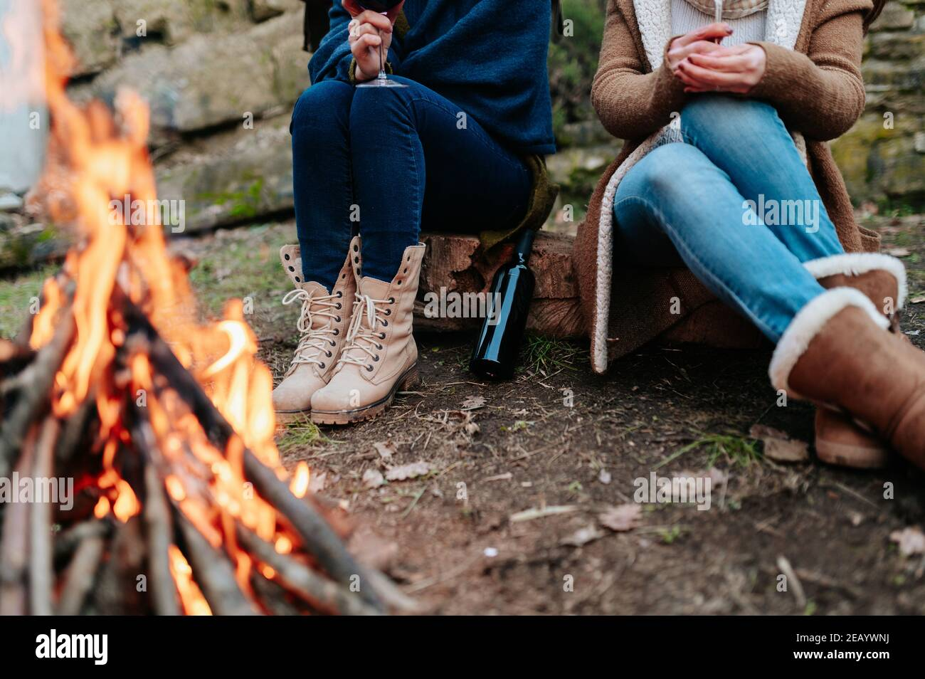 Unrecognizable women holding glass of red wine in campfire warming next to a fire. Stock Photo
