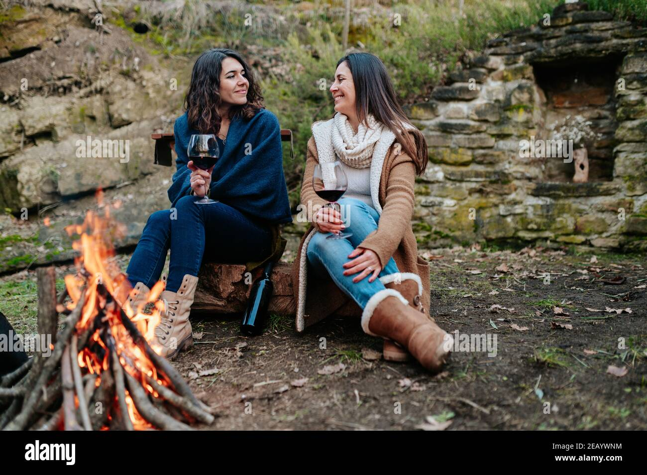 young happy women talking together while drinking glass of red wine. Females warming next to the fire. Campfire, outdoors activities concept. Stock Photo