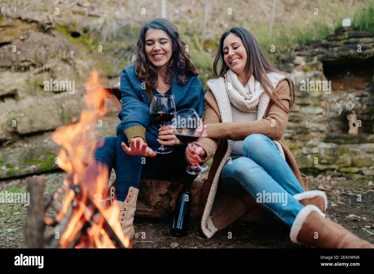 young happy women drinking glass of red wine. Females warming next to the fire. Campfire, outdoors activities concept. Stock Photo