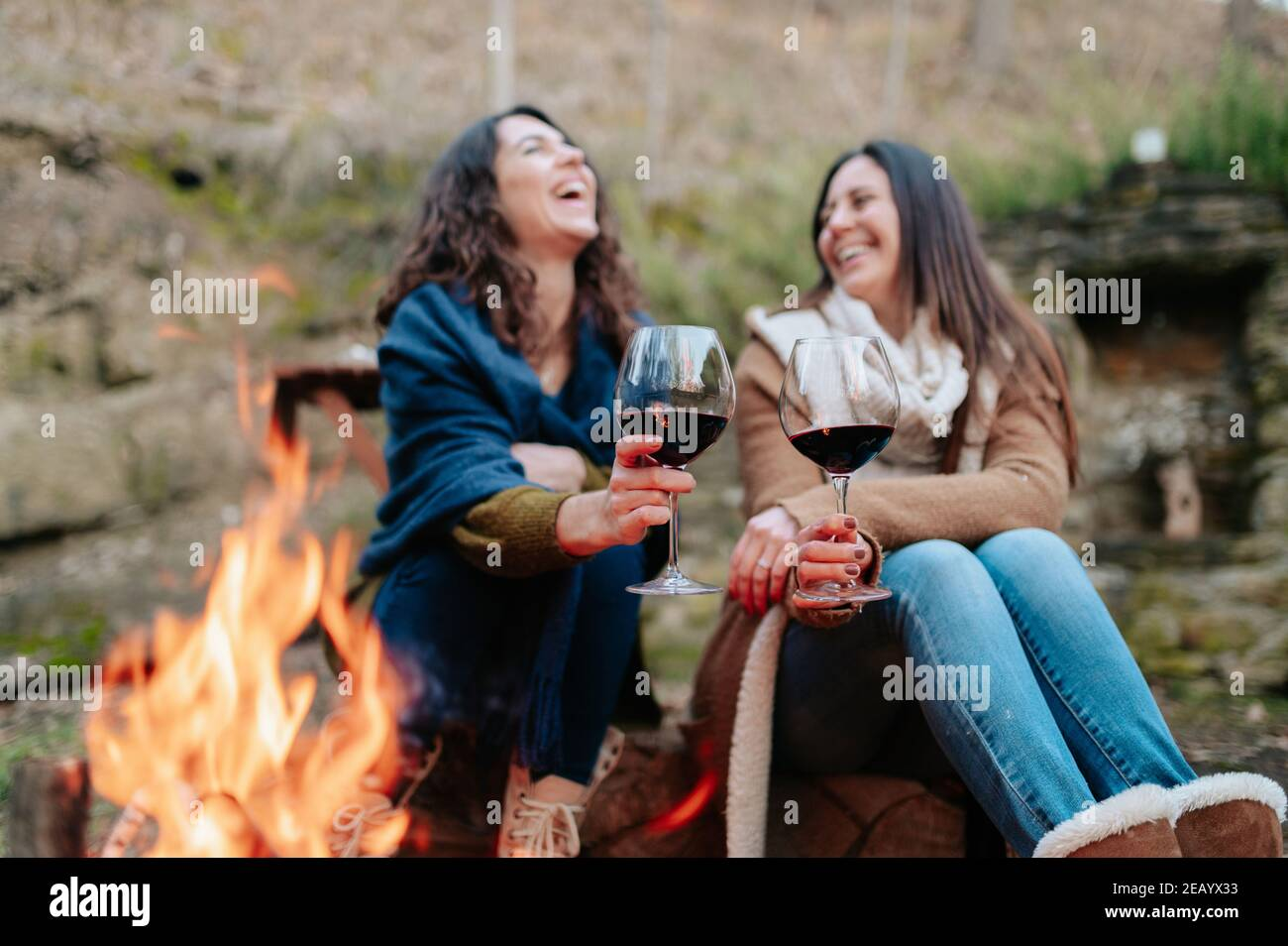 young happy women laughing, holding glass of red wine. Females warming next to the fire. Campfire, outdoors activities concept. Stock Photo