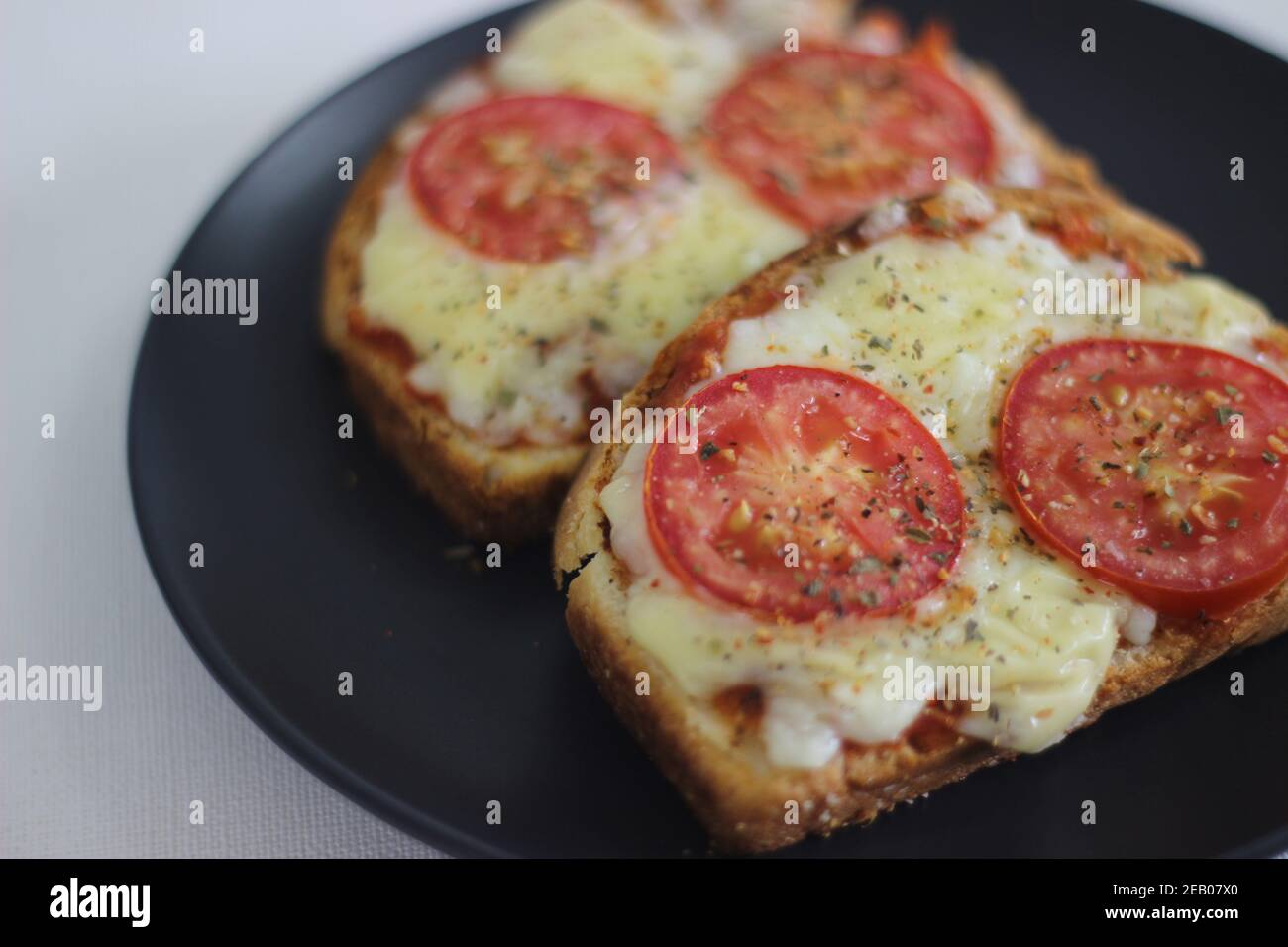 Pizza toast with home baked bread loaf. Shot on white background. Stock Photo