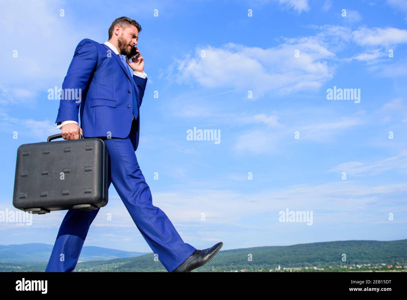 Keep going towards your goal. Businessman formal suit carries briefcase sky background. Businessman solving business problems on phone. Never stop. Entrepreneur in motion purposeful expression. Stock Photo
